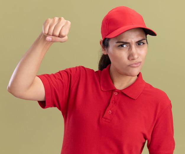 Confiant jeune livreuse en uniforme avec capuchon faisant un geste fort isolé sur mur vert olive
