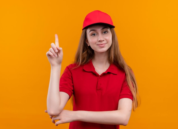 Confiant jeune livreuse en uniforme rouge avec doigt levé sur l'espace orange isolé
