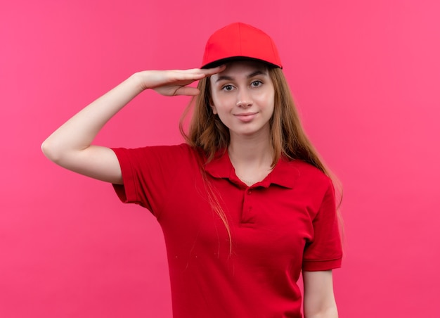 Confiant jeune livreuse en uniforme rouge mettant la main près du front sur l'espace rose isolé