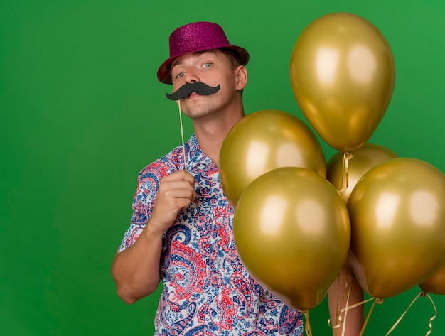 Confiant jeune mec portant chapeau rose tenant des ballons mettant la fausse moustache sur bâton isolé sur vert
