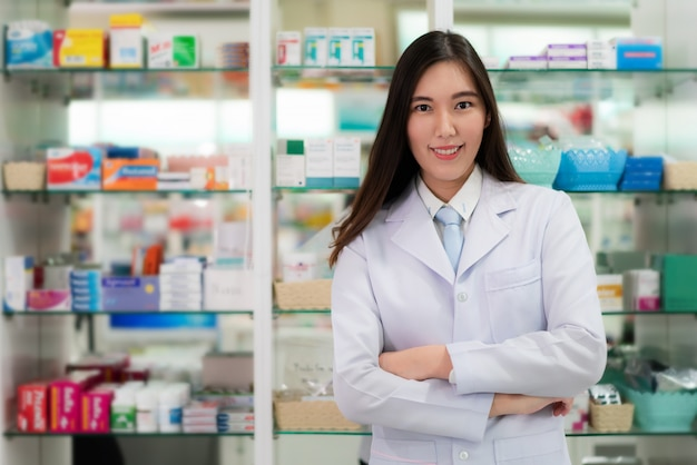 Confiant jeune pharmacien asiatique avec un joli sourire amical debout avec les bras croisés dans la pharmacie de la pharmacie. concept de médecine, de pharmacie, de soins de santé et de personnes.