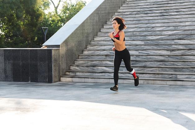 Confiant jeune sportive qui descend les escaliers à l'extérieur