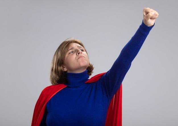 Confiant jeune superwoman blonde en cape rouge levant le poing en le regardant isolé sur mur blanc