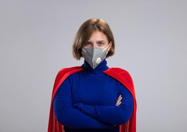 Confiant jeune superwoman blonde en cape rouge portant un masque de protection debout avec une posture fermée à l'avant isolé sur un mur blanc