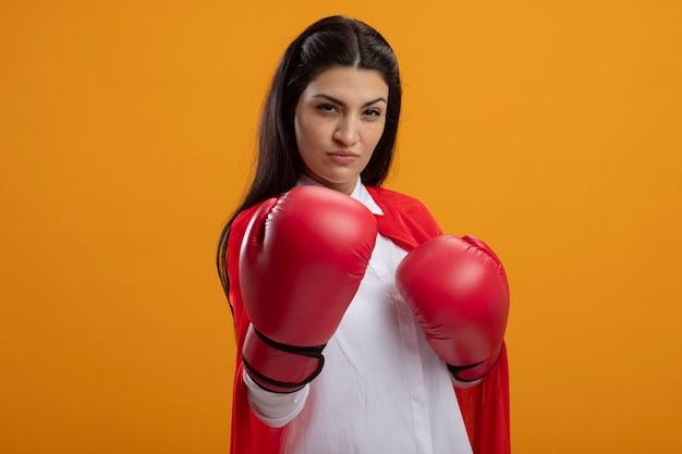 Confiant jeune superwoman portant des gants de boîte à l'avant en étirant la main vers l'avant isolé sur mur orange