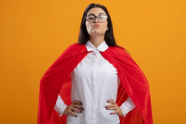 Confiant jeune superwoman portant des lunettes en gardant les mains sur la taille à l'avant faisant baiser geste isolé sur mur orange