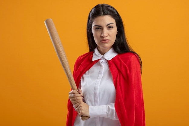 Confiant jeune superwoman tenant une batte de baseball à l'avant isolé sur mur orange
