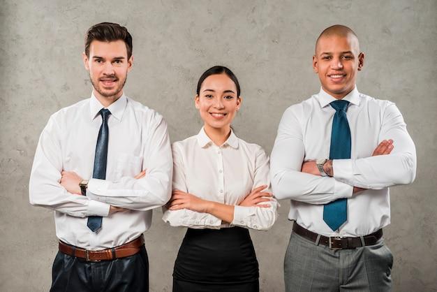 Confiant jeunes hommes d'affaires et femme d'affaires avec les bras croisés à la recherche d'appareil photo