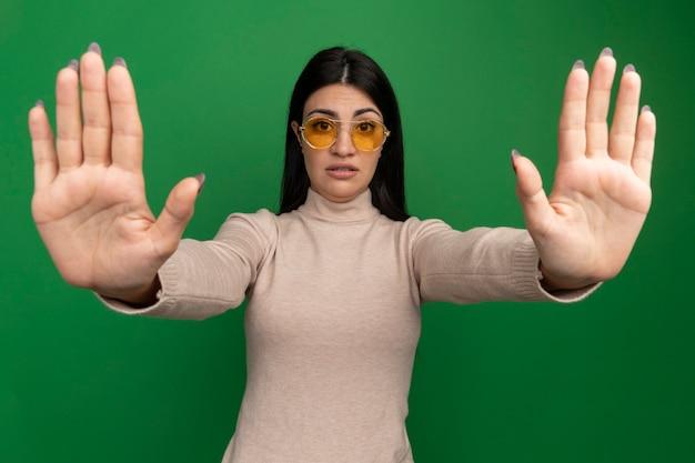 Confiant jolie brune fille caucasienne dans les gestes de lunettes de soleil arrêt signe de la main avec deux mains sur le vert
