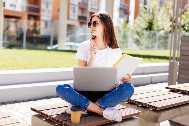 Confiant jolie femme assise sur un banc dans le parc et la messagerie dans les médias sociaux lors de l'écriture dans le cahier pendant la pause-café
