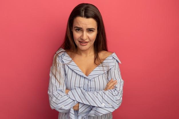 Confiant jolie femme caucasienne debout avec les bras croisés sur rose