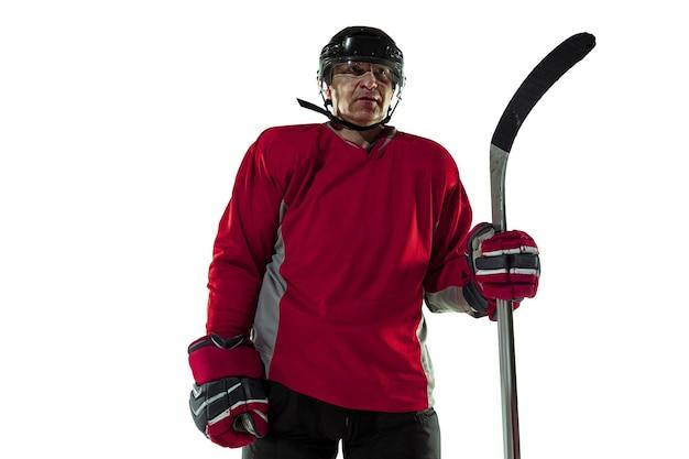 Confiant. joueur de hockey masculin avec le bâton sur le court de glace et le fond blanc. sportif portant un équipement et un casque pratiquant. concept de sport, mode de vie sain, mouvement, mouvement, action.