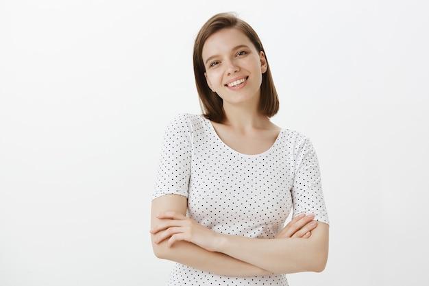 Confiant joyeuse étudiante croise la poitrine des bras et l'air heureux