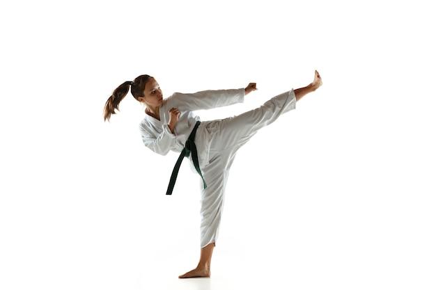 Confiant junior en kimono pratiquant le combat au corps à corps