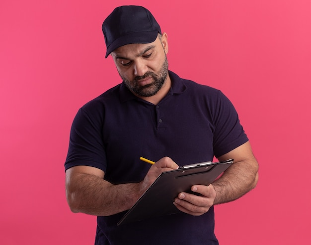 Confiant livreur d'âge moyen en uniforme et cap écrit quelque chose sur le presse-papiers isolé sur mur rose