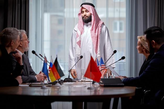 Confiant orateur arabe en robe traditionnelle expliquant son opinion aux partenaires, autres dirigeants lors d'une réunion multiethnique au bureau, à l'aide de microphones pour prononcer