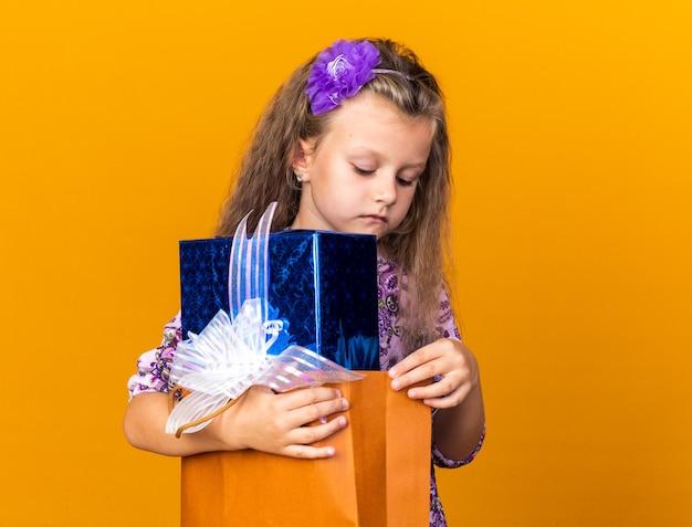 Confiant petite fille blonde tenant et regardant la boîte-cadeau isolé sur un mur orange avec copie espace