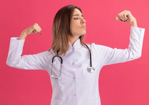 Confiant en regardant une jeune femme médecin portant une robe médicale avec un stéthoscope montrant un geste fort isolé sur un mur rose