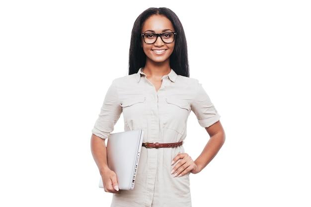 Confiant et réussi. confiante jeune femme africaine à lunettes portant un ordinateur portable et souriant en se tenant debout sur fond blanc