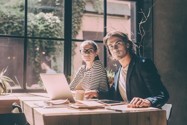 Confiant et réussi. jeune homme et femme confiants regardant la caméra alors qu'ils étaient tous les deux assis au bureau en bois dans un bureau créatif