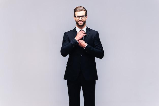 Confiant et réussi. prise de vue en studio d'un beau jeune homme en costume complet ajustant sa cravate et regardant la caméra avec le sourire