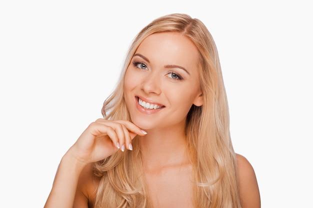 Confiant en sa beauté. souriante jeune femme torse nu tenant la main sur le menton et