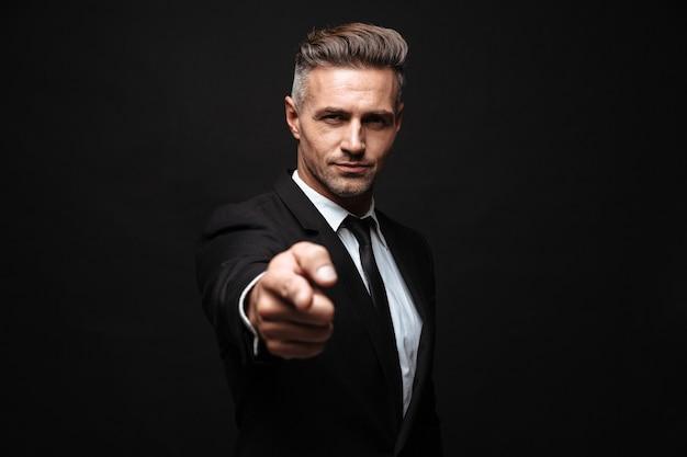 Confiant, séduisant, homme affaires, porter, costume, debout, isolé, sur, mur noir, doigt pointé, appareil-photo