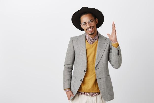 Confiant séduisant homme afro-américain levant la main, le bénévolat, ont des questions
