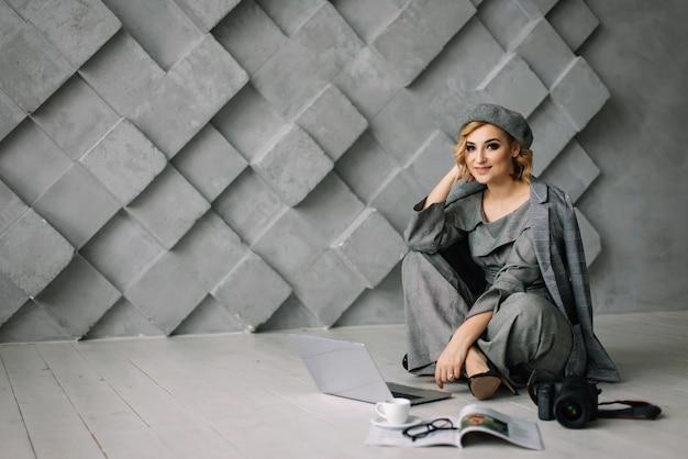 Confiant séduisante jeune femme d'affaires dans des vêtements élégants travaillant sur un ordinateur portable assis sur le sol. le concept de femmes fortes.