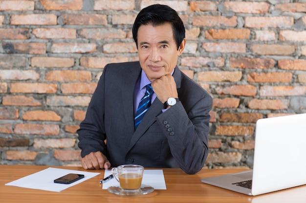 Confiant senior business man assis au bureau
