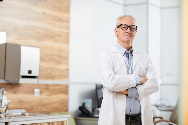 Confiant senior doctor avec bras croisés