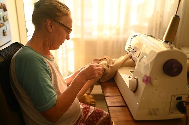 Confiant senior femme âgée couturière chemise blanche et lunettes assis devant la machine à coudre, travaillant sur des vêtements à la maison en utilisant un tissu beige.