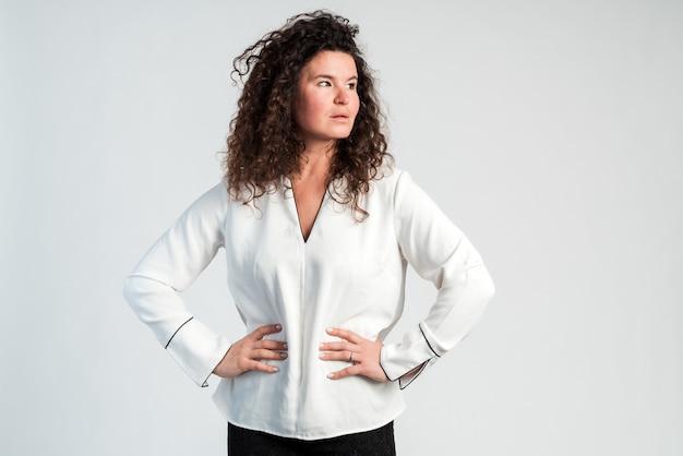 Confiant et sérieux. femme brune bouclée regardant loin et tenant deux mains à sa taille. prise de vue en studio, isolé sur fond blanc