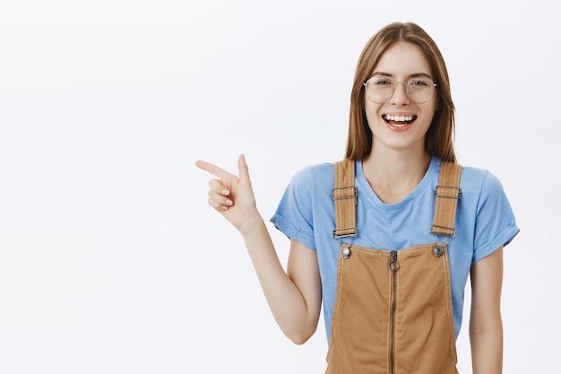 Confiant souriant étudiant jolie fille dans des verres à la recherche de plaisir, pointant le doigt à gauche sur votre logo