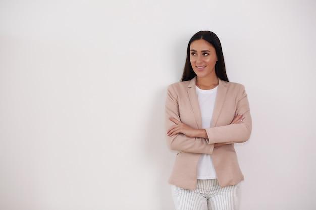 Confiant souriant jeune femme d'affaires élégante en costume vêtements regardant la caméra isolée sur fond gris studio,
