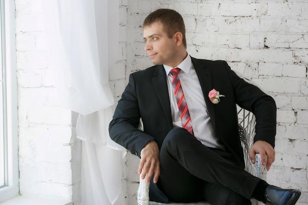 Confiant souriant jeune homme d'affaires assis sur une chaise blanche
