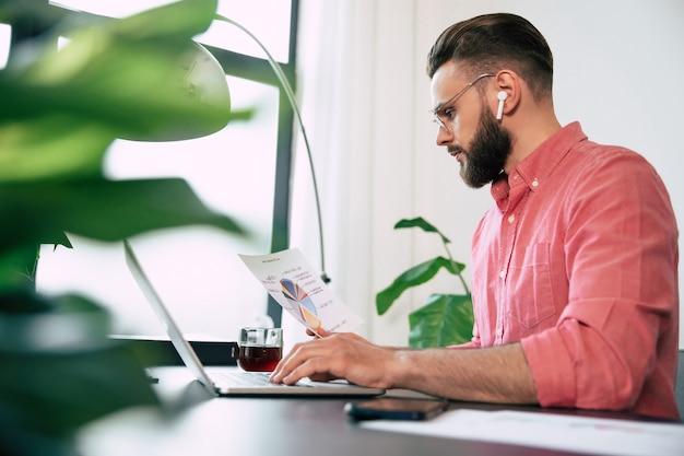 Confiant succès bel homme barbu dans des lunettes et des vêtements décontractés intelligents travaille sur l'ordinateur portable
