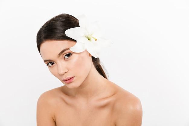 Confiante belle femme à moitié nue avec fleur de lys dans les cheveux