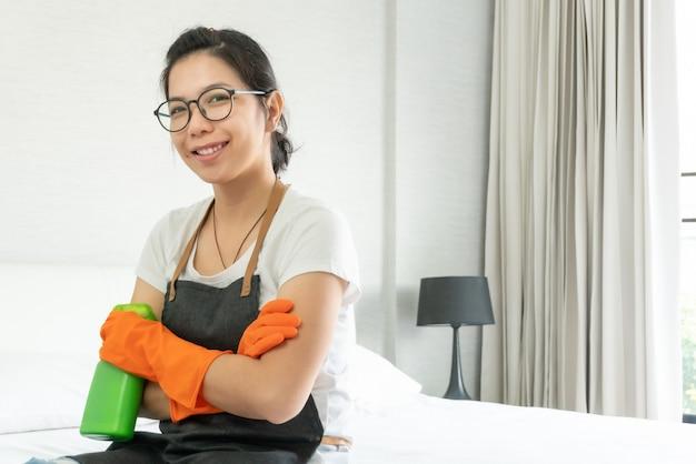 Confiante femme asiatique souriante en tablier gris et gants en caoutchouc orange préparant le nettoyage de sa chambre.