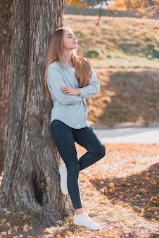 Confiante femme blonde posée sur un arbre