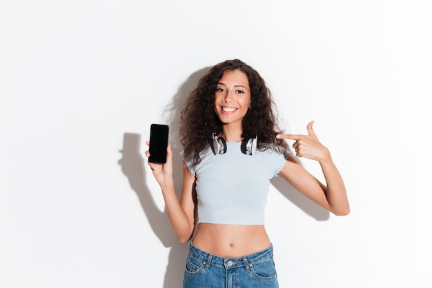 Confiante femme joyeuse pointant sur smartphone