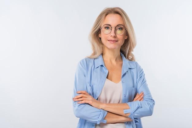 Confiante jeune femme blonde avec les bras croisés, debout sur un fond blanc