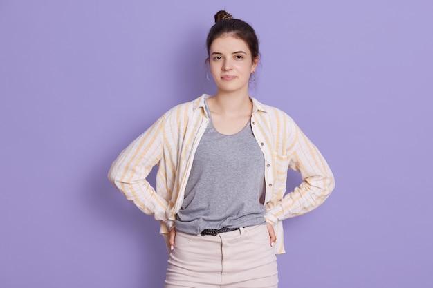 Confiante jeune femme brune avec chignon se dresse et regarde directement la caméra avec un regard sérieux
