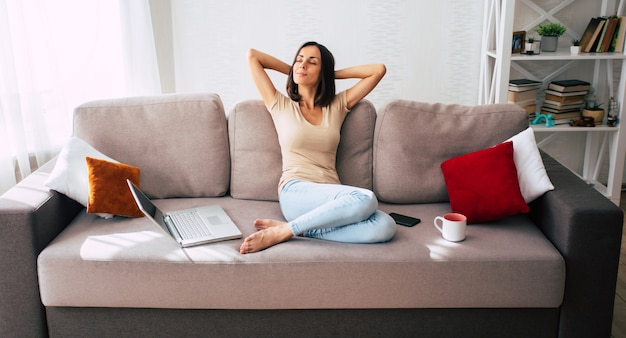 Confiante jeune femme mignonne moderne travaille en ligne et se détend à la maison sur le canapé avec son ordinateur portable sur le travail indépendant