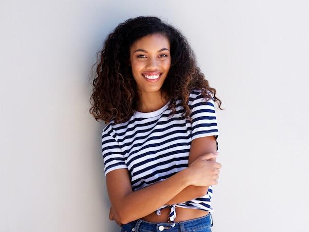 Confiante jeune femme noire souriante contre le mur blanc