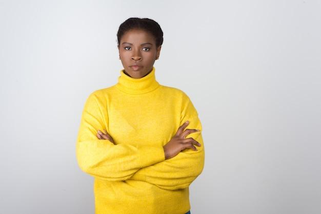Confiante jeune femme en pull jaune