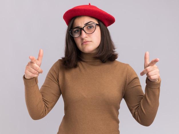 Confiante jeune jolie fille caucasienne avec chapeau de béret et lunettes optiques pointant vers la caméra à deux mains