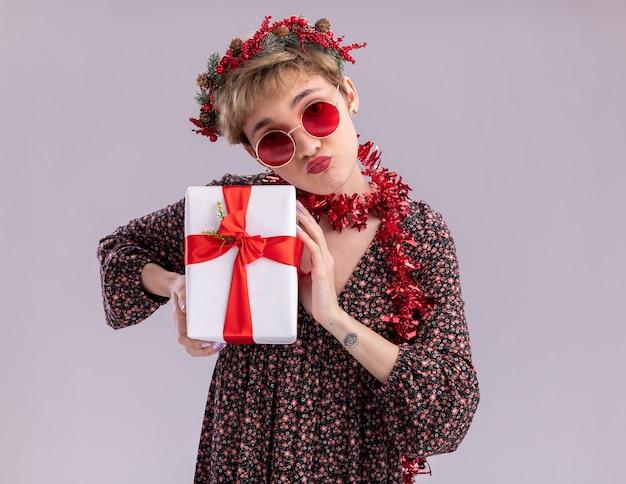 Confiante jeune jolie fille portant une couronne de noël et une guirlande de guirlandes autour du cou avec des lunettes tenant un paquet cadeau avec des lèvres pincées isolées sur un mur blanc avec un espace de copie