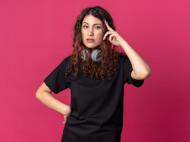 Confiante jeune jolie fille portant des écouteurs sur le cou en gardant la main sur la taille faisant un geste de réflexion isolé sur un mur cramoisi