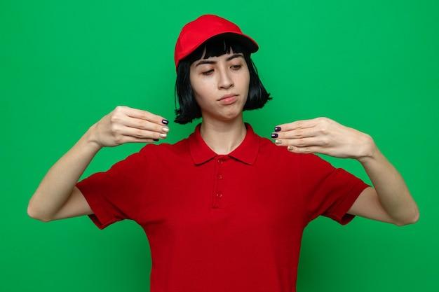 Confiante jeune livreuse caucasienne faisant semblant de tenir quelque chose et regardant ses mains